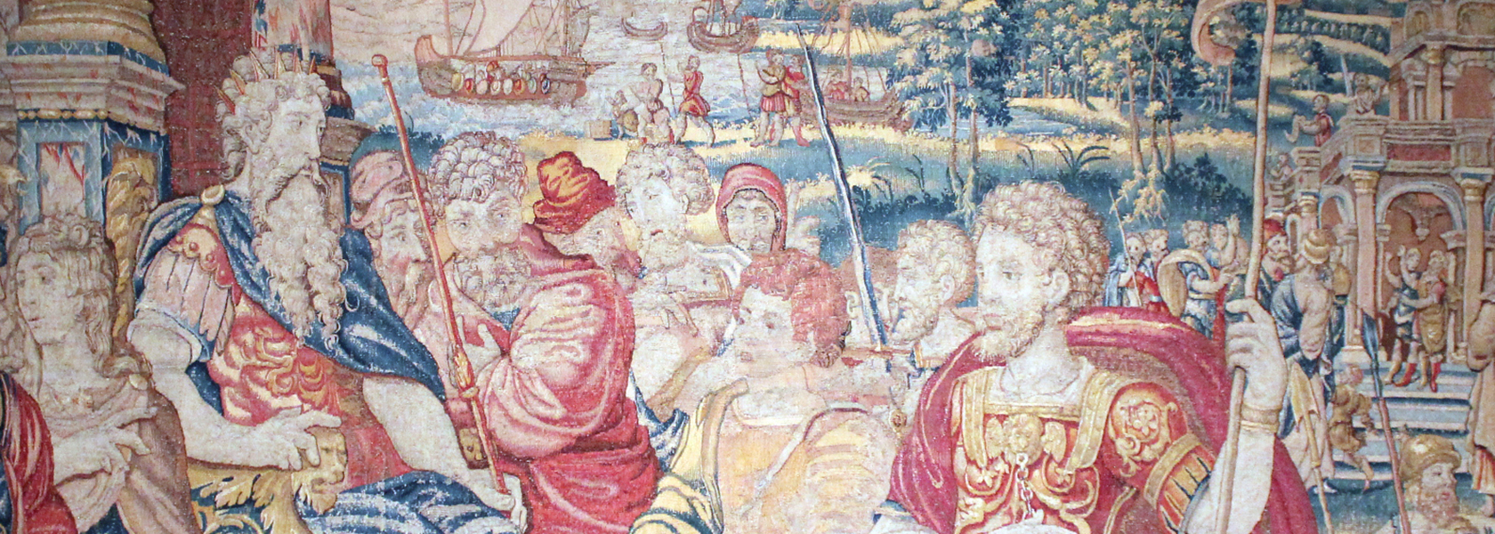 A detail shot of the tapestry featuring a warrior dressed in red, gold and blue holding a spear